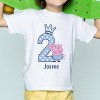 a front view smiling litttle boy in white t-shirt holding skateboard on the blue desk